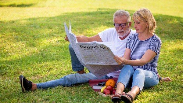 老人在草地上看报纸